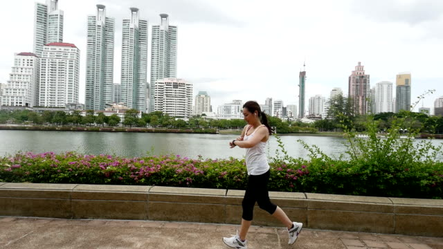SLO MO Fitness woman runner running and watching Smart watch in City