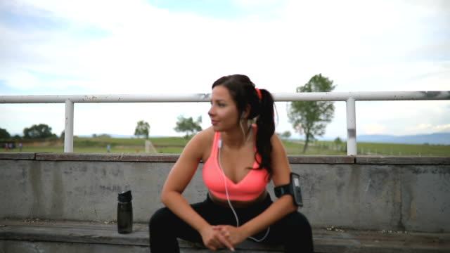stockvideo's en b-roll-footage met fitness vrouw nemen van een pauze zit op stappen worden uitgevoerd. - resting