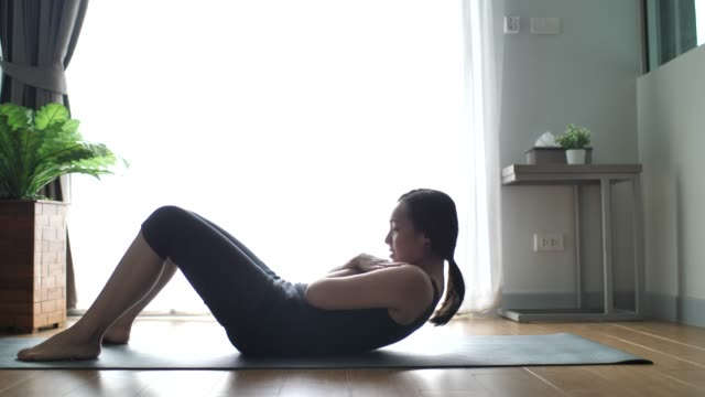 fitness woman woman exercising at home - sit ups stock videos & royalty-free footage