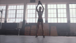 Fitness woman working out with kettle bell at gym