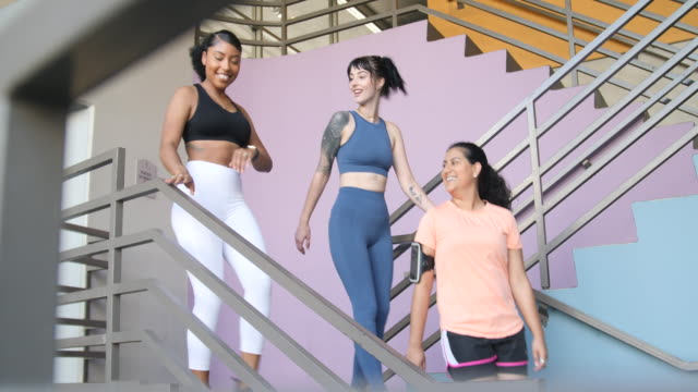 fitness women walking down the stairs - ventenne video stock e b–roll
