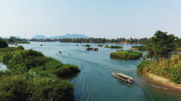 Five boats cross the islands of the Mekong River, in Don Det, 4000 islands, Laos on a summer day.