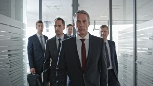 Five businessmen walking down the hall and into the office for a meeting
