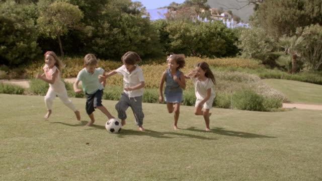 Five children kicking soccer ball in park