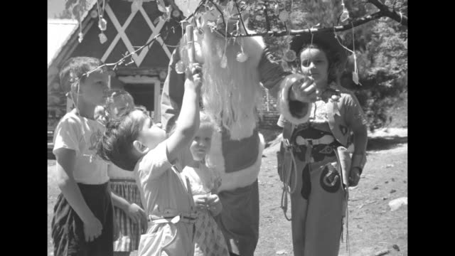 five children, one wearing cowboy outfit, exit alpine-type cabin with santa claus / they all walk to tree with lollipops hanging from its branches,... - lollipop stock videos & royalty-free footage