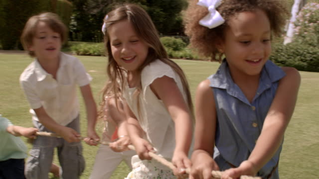 five children pulling rope having tug of war in park - pulling stock videos & royalty-free footage