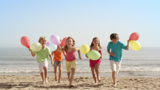 Five children running towards camera on beach holding balloons.