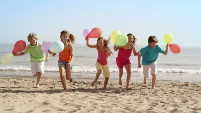 five children running towards camera on beach holding balloons. - five people stock videos & royalty-free footage