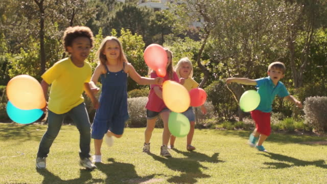 Five children running towards camera with balloons.
