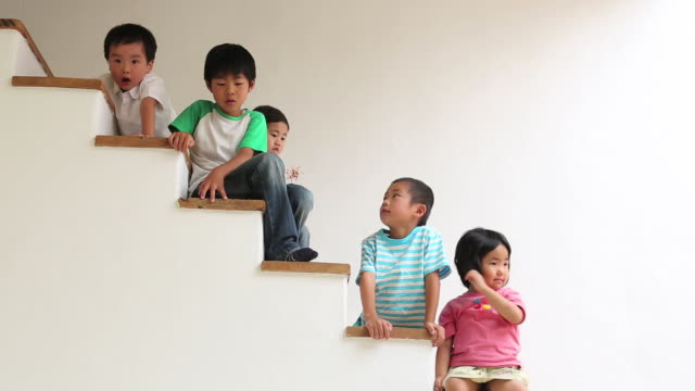 five children sitting and frolicing on stairs at home,seen from side - kindergartengebäude stock-videos und b-roll-filmmaterial