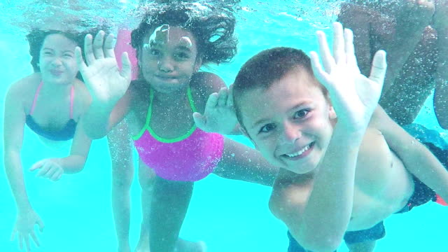 five children underwater swimming toward camera - swimming stock videos & royalty-free footage