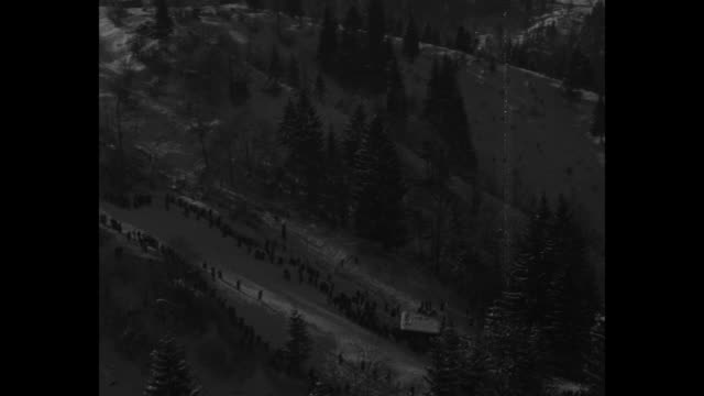 vídeos de stock, filmes e b-roll de five circles frame shots of skiers moving down incline / pan snowy mountains and ski course / pan stadium with people filing in / vs skiers move and... - montanhas wetterstein