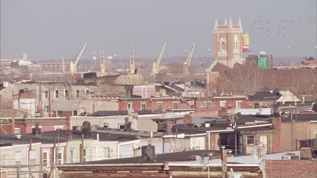 five cranes stand in the distance beyond a working-class neighborhood. - steeple stock videos & royalty-free footage