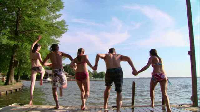 WS five friends holding hands and jumping off dock into lake/ Texas