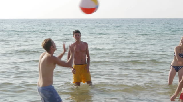 vidéos et rushes de five friends playing with beach ball in sea - 16 17 ans