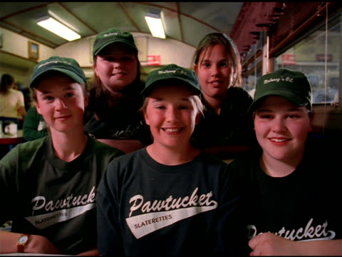 five girls in baseball caps and uniform pose for camera in diner, pawtucket - baseballspieler stock-videos und b-roll-filmmaterial