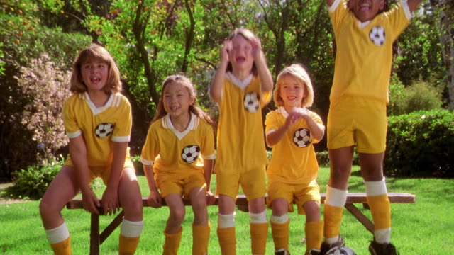 vidéos et rushes de five girls on soccer team jumping up from bench on sidelines + cheering - banc