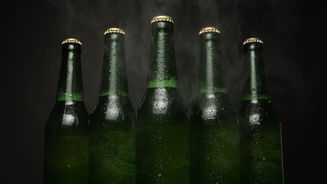 vídeos de stock, filmes e b-roll de cinco garrafas de cerveja verde em pé um por um em um fundo preto - frio