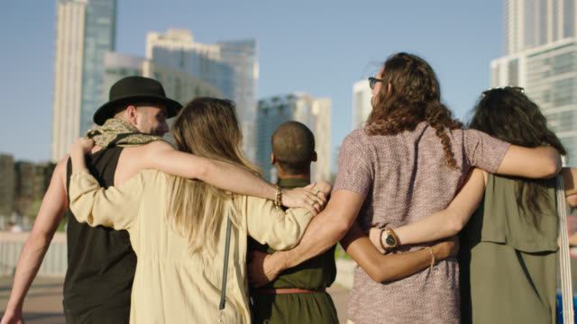 vidéos et rushes de slo mo. five hipster friends walk arm in arm on pfluger pedestrian bridge towards downtown austin city skyline. - d'ascendance européenne