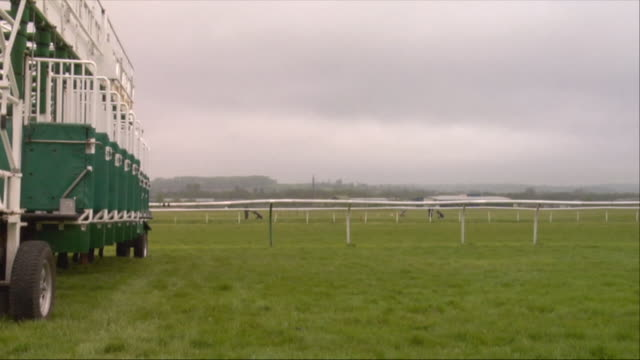 sm ws five jockeys on horses running out of starting gates during race at newbury racecourse / newbury, england, uk - newbury inghilterra video stock e b–roll