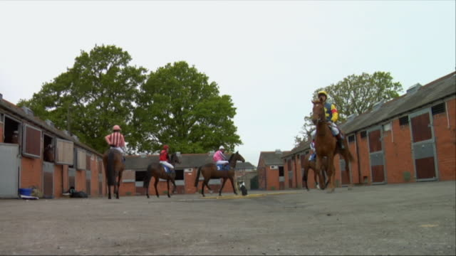 la ws five jockeys on horses walking near stables / newbury, england, uk - see other clips from this shoot 1045 stock videos and b-roll footage