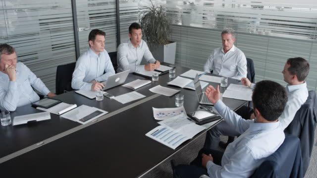 Five male colleagues in a meeting with their project leader in the conference room