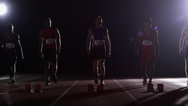 Five male track athletes approach the starting line and get into position for a race.