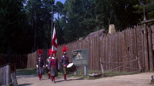 ms pan five man patrol in period english costume marching through entranc - bandiera inglese video stock e b–roll