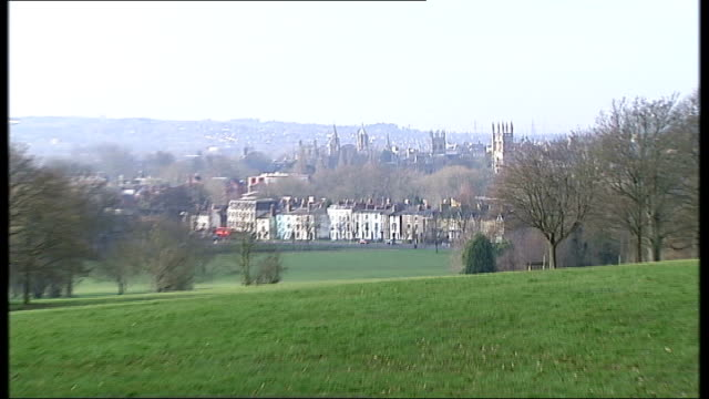 five members of oxford gang jailed for grooming underage girls; t20021319 / tx 3 oxford: ext bench in park zoom in oxford cityscape oxford buildings... - turmspitze stock-videos und b-roll-filmmaterial