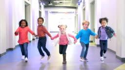Five multi-ethnic preschool children holding hands