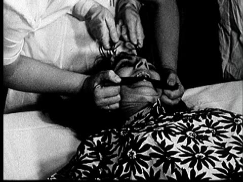 1953 FILM MONTAGE Five nurses and doctor surrounding patient on hospital bed/ CU woman gagged as electrodes are placed on her forehead/ PAN up to doctor giving shock therapy/ Norman, Oklahoma