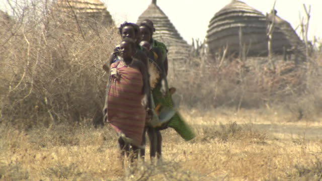 Five pregnant women walking across dry field in South Sudan