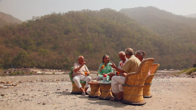 Five senior people drinking juice at riverbank, Ganges River, Rishikesh, Uttarakhand, India