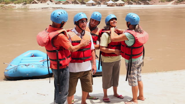 five senior people ready for white water rafting, ganges river, rishikesh, uttarakhand, india - helm stock-videos und b-roll-filmmaterial