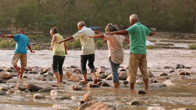 Five senior people walking at riverbank, Ganges River, Rishikesh, Uttarakhand, India