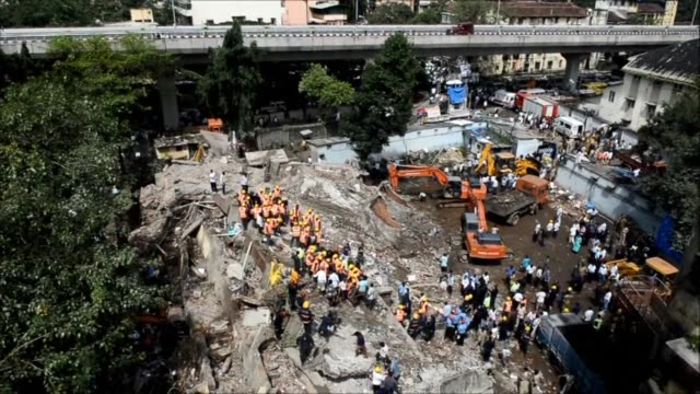 a five storey residential block collapses in mumbai killing at least three people and leaving dozens feared trapped inside in the latest building... - building storey stock videos and b-roll footage