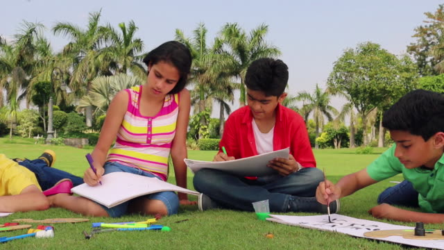 Five teenage boys and girls doing painting in the park, Delhi, India