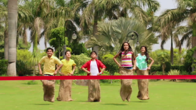 five teenage boys and girls playing sack race in the park, delhi, india - sack race stock videos & royalty-free footage