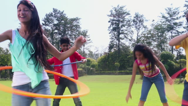 five teenage boys and girls playing with hula hoop in the park, delhi, india - teenage boys stock videos & royalty-free footage
