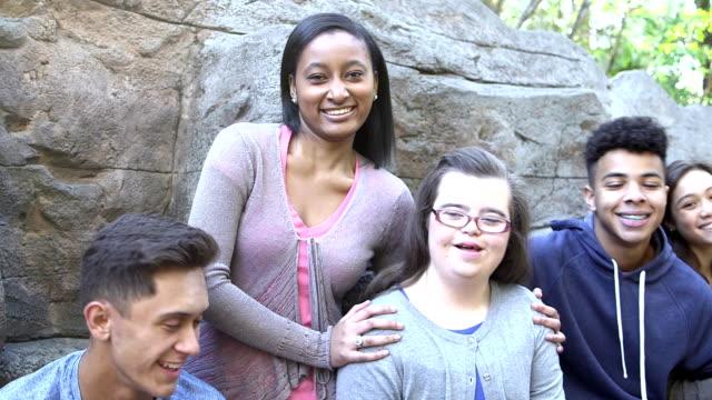 fünf jugendliche im park von felswand, mädchen mit down-syndrom - multi ethnic group stock-videos und b-roll-filmmaterial