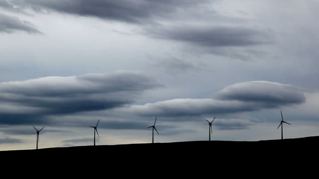 Five wind turbines on a hill.