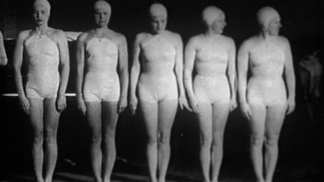 b/w five women in identical bathing suits + caps standing on side of pool (synchronized swimming) - cuffia da nuoto video stock e b–roll