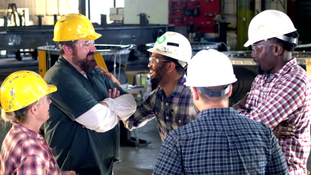 five workers meeting on factory floor, laughing - work helmet stock videos & royalty-free footage