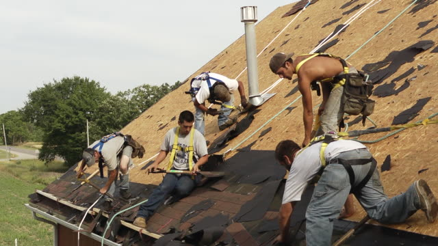 ms five workers removing shingles on roof of red building / chelsea, michigan, united states - garden fork stock videos & royalty-free footage