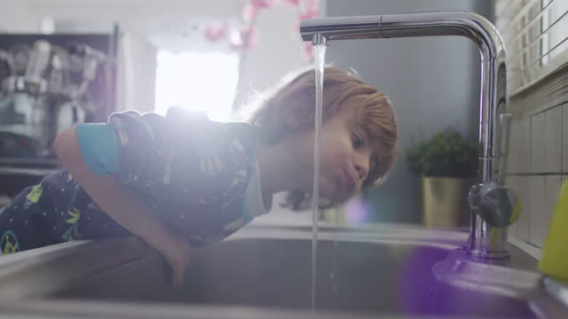 vídeos de stock, filmes e b-roll de five year old boy drinking water at a sink in the kitchen - 4 5 anos