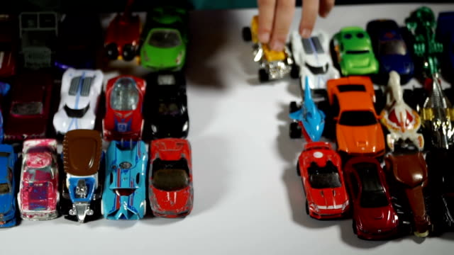 five year old boy playing with toy cars - 集める点の映像素材/bロール