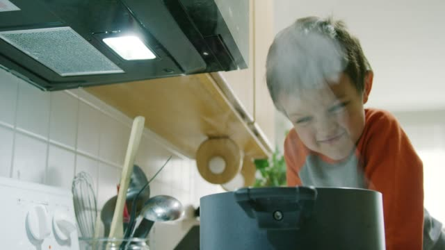 A Five Year-Old Caucasian Boy Acts Silly and Makes Faces at a Steaming Pot that Is Sitting on a Stove Top Range in a Kitchen