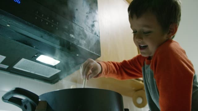 a five year-old caucasian boy sits on the counter in the kitchen and stirs liquid in a large pot that is sitting on a stove top range - danger stock videos & royalty-free footage