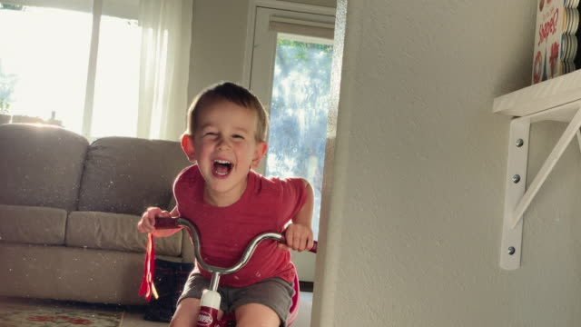 a five year-old caucasian boy surprises his three year-old caucasian brother riding a tricycle who then laughs as the two boys play with each other indoors in a house - tricycle stock videos & royalty-free footage