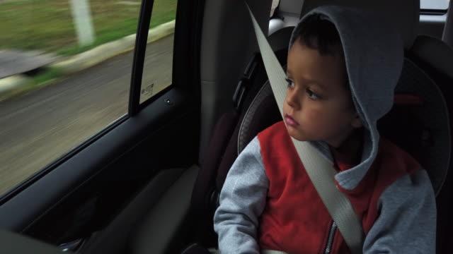 5歳の白人の男の子がパーカーとシートベルトをしていて、彼の carseat に座り、動いている乗り物の窓から外を見る - シートベルト点の映像素材/bロール